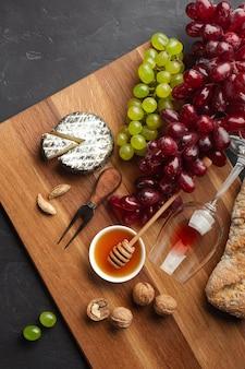Käsekopf, weintraube, honig, nüsse und weinglas auf holzbrett und schwarzem hintergrund. draufsicht mit kopienraum.