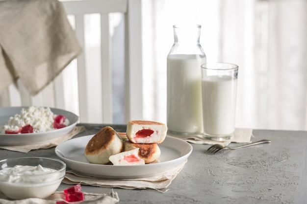 Käsekuchen aus hüttenkäse mit himbeermarmelade auf einem teller mit sauerrahm und einem glas milch.
