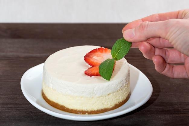 Käsekuchen-kuchen mit frischen erdbeeren auf weißem teller. frauenhand dekorierte kuchen eine minze.