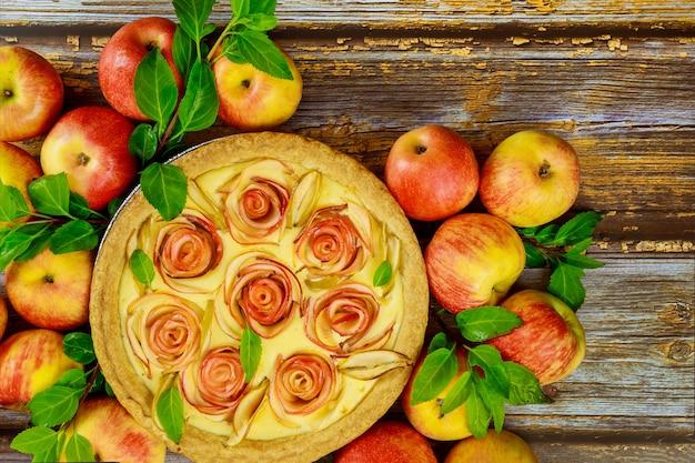 Käsekuchen mit apfelform in rosenform und frischen äpfeln. draufsicht.