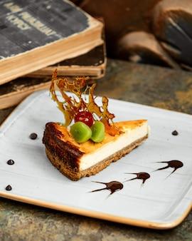 Käsekuchen mit einer scheibe kiwi-glasierter kirsche und karamellisiertem zucker