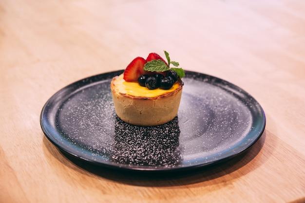 Käsekuchen mit erdbeer-brombeer-scheiben und puderzucker