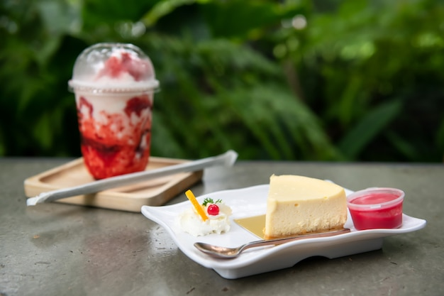 Käsekuchen mit erdbeersauce und milchbeeren-smoothie auf dem tisch mit grünem blatthintergrund. bäckerei und süßes dessertrestaurant im gartenpark im freien.