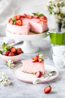 Käsekuchen mit frischen erdbeeren auf einem weißen tisch. selektiver fokus