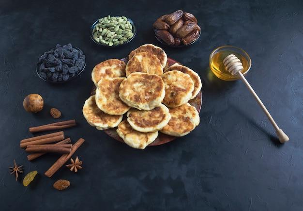 Käsekuchen mit honig, datteln und kaffee auf dem tisch.