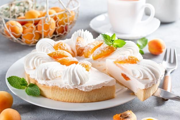 Käsekuchen mit joghurt und aprikose auf hellem hintergrund. aprikosenkuchen. früchtekuchen. französisches gebäck