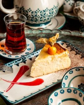 Käsekuchen mit physalis und birnenförmigem glas teontisch