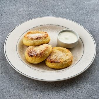 Käsekuchen mit saurer sahne, mit puderzucker auf einem weißen teller bestreuen