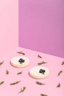 Käsekuchen mit schokoladen-heidelbeer-rosmarin-blättern auf rosa hochwertigem foto