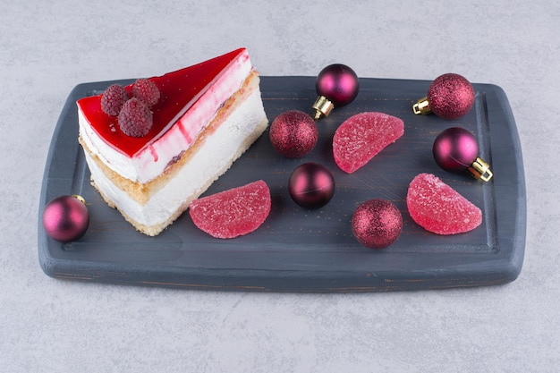 Käsekuchen mit süßigkeiten und weihnachtskugeln auf dunklem teller. foto in hoher qualität
