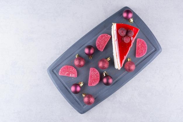 Käsekuchen mit süßigkeiten und weihnachtskugeln auf dunklem teller. hochwertiges foto