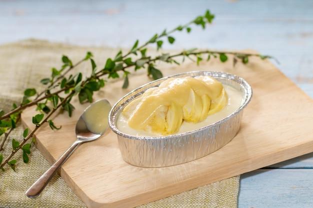 Käsekuchen mit überstiegener durianfrucht und duriancreme auf hölzernem schreibtischhintergrund. sommerfrucht zum nachtisch in thailand und in asien