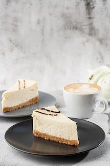 Käsekuchen new york oder klassischer käsekuchen mit tasse kaffee auf weißem tisch. nahaufnahme. leckeres frühstück. stück kuchen auf schwarzem teller, weiße tasse auf weißem marmorhintergrund. vertikales foto.
