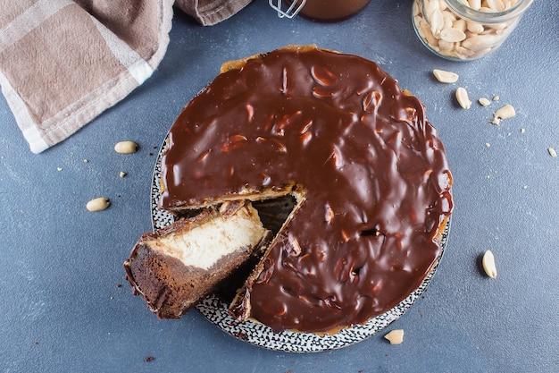 Käsekuchen snickers mit karamell, nougat und erdnuss überlagert kuchen auf blauem konkretem backgro