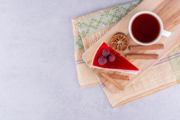 Käsekuchen und eine tasse schwarzen tee auf holzbrett. foto in hoher qualität