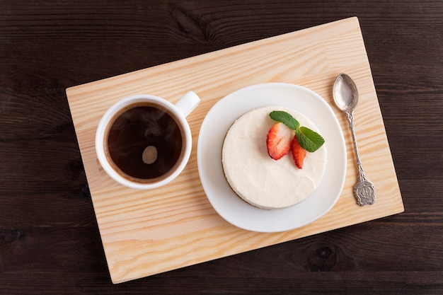 Käsekuchen und tasse kaffee auf holztablett. gutes frühstück. draufsicht