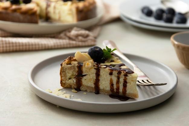 Käsekuchenscheibe mit schokoladensauce und blaubeere in einem teller mit einer gabel auf hellem hintergrund