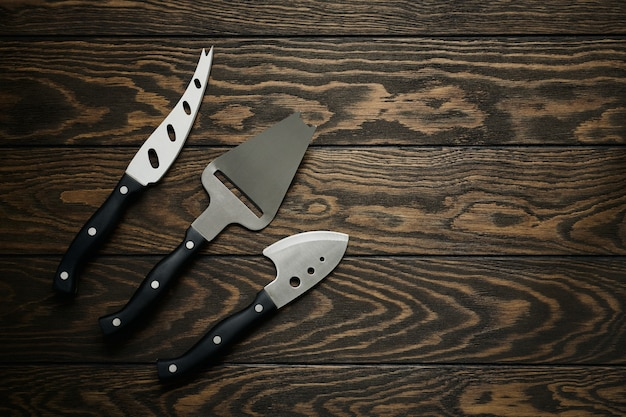 Käsemesser in verschiedenen formen auf dem tisch liegend, holzhintergrund mit kopierraum, flache lage