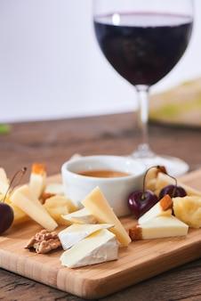 Käsemischung aus parmesan, mozzarella, camembert auf einem holzbrett und einem glas rotwein