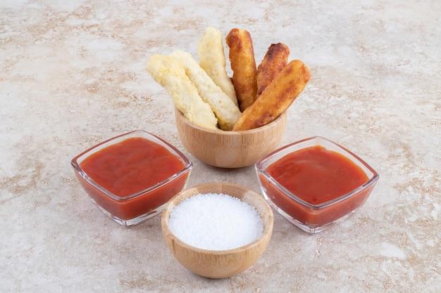 Käsenuggets und gegrillte würstchen mit saucen.