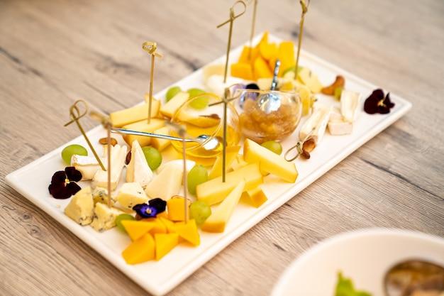 Käseobst und honig auf einem rechteckigen weißen teller catering