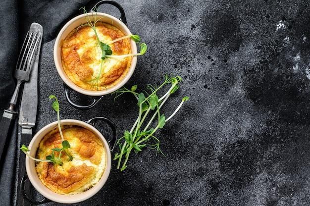 Käseomelett, omelett mit microgreens in einer pfanne. schwarzer hintergrund. draufsicht. speicherplatz kopieren