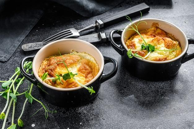 Käseomelett, omelett mit microgreens in einer pfanne. schwarzer hintergrund. draufsicht