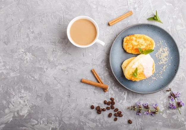 Käsepfannkuchen auf einer blauen keramischen platte und einem tasse kaffee auf grau