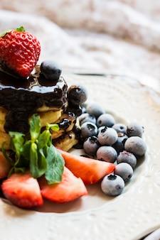 Käsepfannkuchen mit den erdbeeren und blaubeeren bedeckt mit schokolade zum frühstück