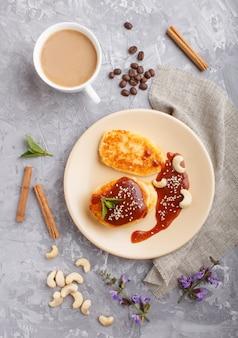 Käsepfannkuchen mit karamellsoße auf einer beige keramischen platte und einem tasse kaffee auf grauem beton