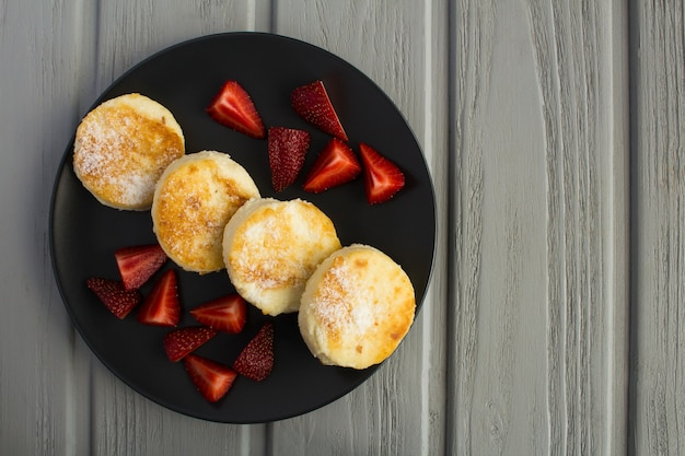 Käsepfannkuchen und erdbeeren auf der dunklen platte auf dem grauen hölzernen hintergrund. draufsicht. kopierraum.