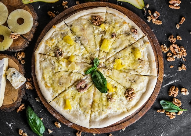 Käsepizza mit birne und nüssen auf einer dunklen oberfläche