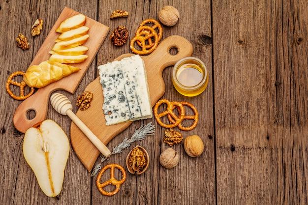 Käseplatte antipasti mit geräuchertem und blauschimmelkäse, crackern, honig, walnüssen und reifer birne. traditionelles snack-rezept