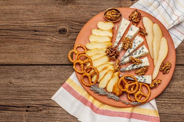 Käseplatte antipasti mit geräuchertem und blauschimmelkäse, crackern, honig, walnüssen und reifer birne.
