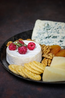 Käseplatte auf dunkelheit mit camembertkäse, blauschimmelkäse, gauda und beeren und imbissen