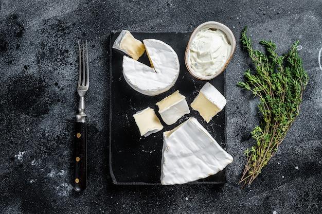 Käseplatte. camembert, brie, gorgonzola und blauschimmelkäse mit thymian. schwarzer hintergrund. ansicht von oben.