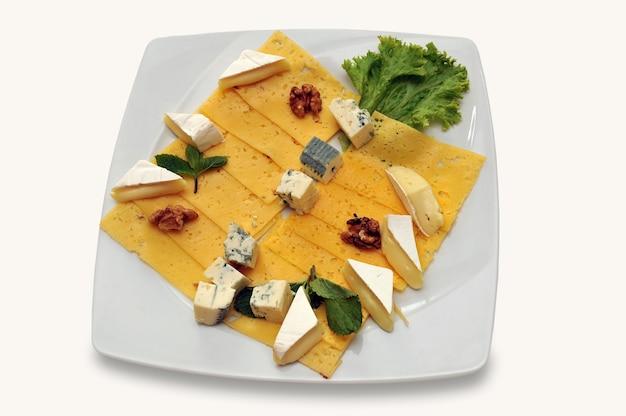 Käseplatte für feinschmecker mit blauem, gealtertem, gelbem und weißem käse, lokalisiert auf weißem hintergrund.