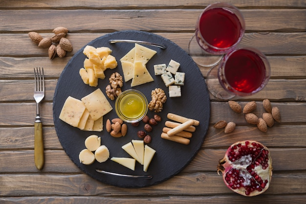 Käseplatte in draufsicht sortiment verschiedener käsesorten auf dunklem schieferbrett