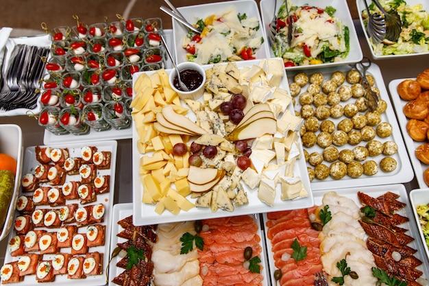 Käseplatte mit anderen snacks auf einem banketttisch