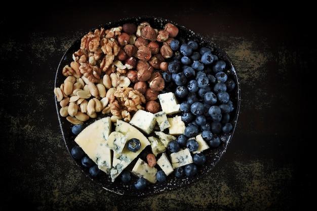 Käseplatte mit blaubeeren und nüssen.