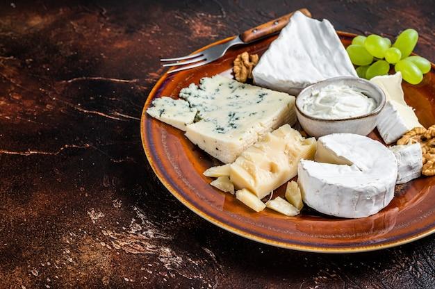 Käseplatte mit brie, camembert, roquefort, blauschimmelkäse, trauben und nüssen. dunkler hintergrund. ansicht von oben. platz kopieren.