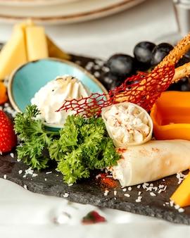 Käseplatte mit crackern und trauben