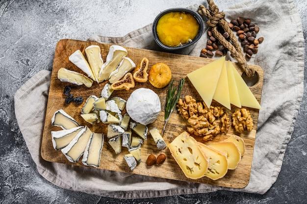 Käseplatte mit französischen bio-käse, feigen, nüssen auf grauem hintergrund. ansicht von oben. leckere käse vorspeise