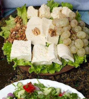 Käseplatte mit grünen trauben und nüssen.