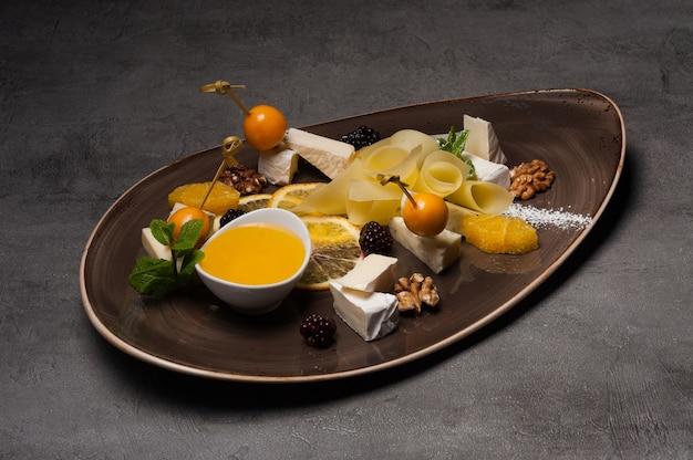 Käseplatte mit honig, orange und brombeeren