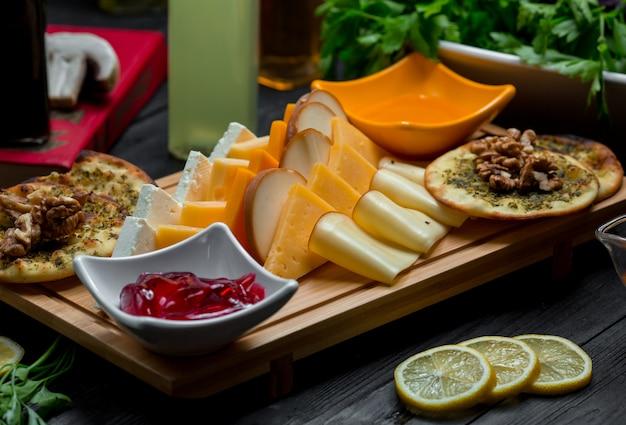 Käseplatte mit käsevariationen, crackern, nüssen und erdbeermarmelade