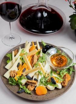 Käseplatte mit nüssen rosinen rucola oliven und glas wein