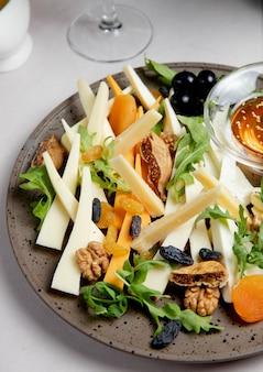 Käseplatte mit nüssen rosinen rucola und oliven