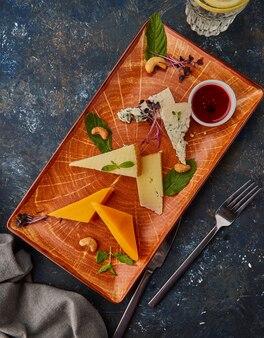 Käseplatte mit nüssen und marmelade. teller mit verschiedenen käsesorten