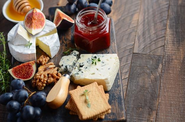 Käseplatte mit trauben, feigen, crackern, honig, pflaumengelee, thymian und nüssen